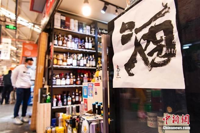 水墨畫藝術家邱志傑,在北京市朝陽區三源里菜市場,舉辦名為「民以食為天」的書法展。(摘自中新網)