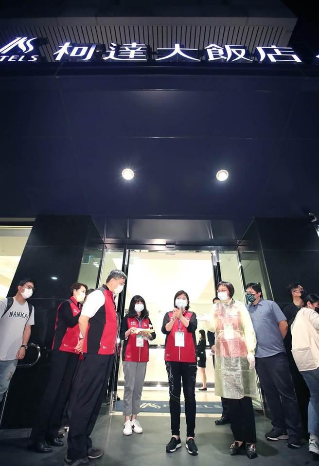 台北市长柯文哲(左)6日因应华航机师、诺富特饭店发生群聚事件,前往台北市的防疫饭店之一柯达饭店视察,针对北市102家防疫旅馆是否确实做好防疫标准作业流程(SOP)进行总体检,图为柯文哲在进入饭店前,观看工作人员示范穿着防护衣。(郑任南摄)