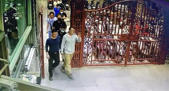 身穿灰白上衣、綁著馬尾的阮姓男子被警方逮捕,仍神情自然的微笑與社區保全揮手、打招呼。(民眾提供/林欣儀台中傳真)