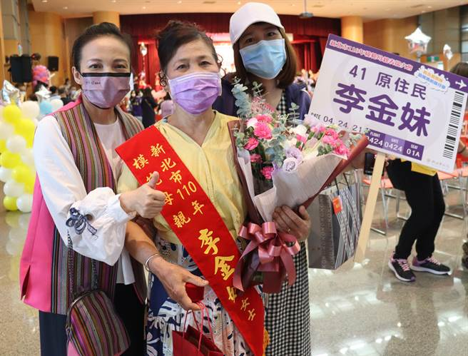 羅美菁局長(左一)贈花祝賀阿美族李金妹女士(中)獲模範母親。(原民局提供)