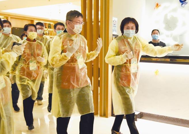 台北市長柯文哲(中)6日因應華航機師、諾富特飯店發生群聚事件,穿上防護衣前往台北市的防疫飯店之一柯達飯店視察。(鄭任南攝)