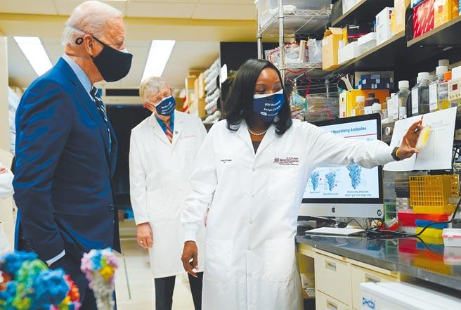 為因應全球新冠疫情,美國拜登政府支持暫時豁免與新冠疫苗相關的智慧財產權保護。圖為拜登(左)今年2月11日走訪國家衛生院(NIH)病毒發病機制實驗室,並聽取NIH疫苗研究中心免疫學家介紹新冠疫苗的相關研究。(美聯社)