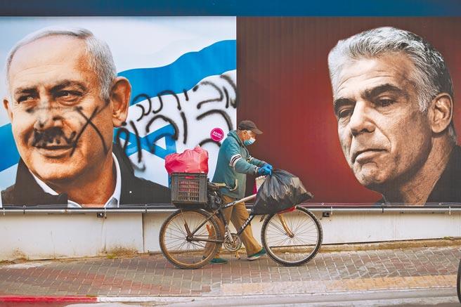 今年3月以色列國會選舉期間,特拉維夫東邊的拉馬特甘市街頭,以國總理納坦雅胡(左)的競選看板遭人塗鴉,右邊則是在野「未來黨」黨魁拉皮德(右)的看板。(美聯社)