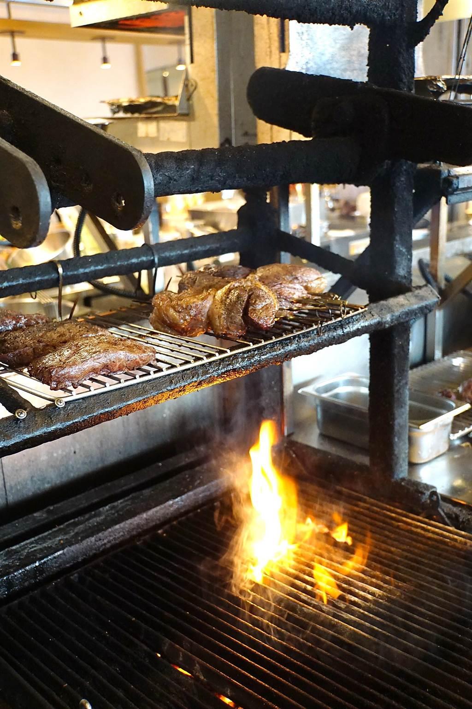 松山意舍〈Que〉餐廳的牛、豬、羊排,都是以原木直火燒烤,且客人看得到燒烤過程。(圖/姚舜)