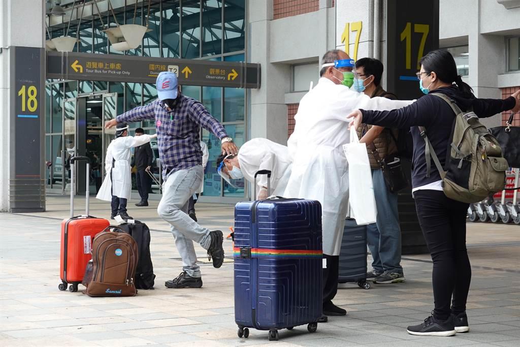 搭乘日航專機自印度返台的旅客,8日中午抵達台北松山機場,經防疫消毒後,乘坐遊覽車前往集中檢疫所。(姚志平攝)