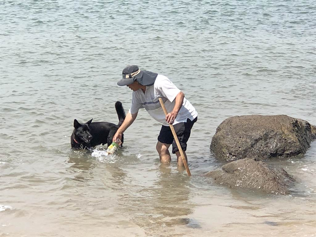 家住前水頭的金門酒廠老員工葉福和在今年2月4日,帶家中大黑狗「多多」到塔山電廠前方海灘玩,意外發現這顆奇怪的石頭。(李金生攝)
