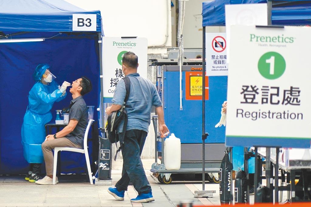 香港政府7日宣布,自5月12日起,只要完成接種兩劑新冠疫苗、並與接種第二劑相隔14天以上,無論是香港市民或境外人士入港者,強制檢測期均可縮短。圖為香港市民在香港入境事務大樓旁的流動採樣站參加強制檢測。(中新社)