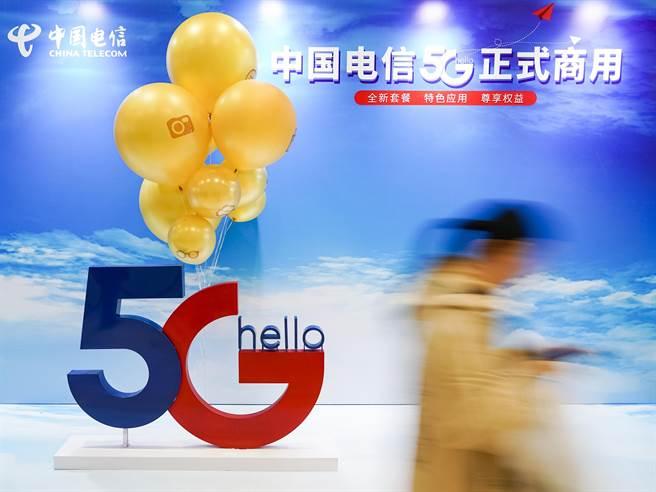一名消費者走過中國電信5G正式商用的廣告展板。(圖/本報資料照)