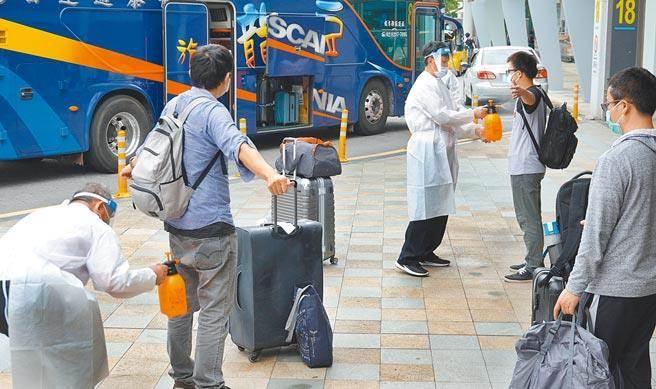 搭乘日本航空自印度返台的旅客,8日中午抵達台北松山機場,經防疫人員協助消毒後,乘坐遊覽車前往集中檢疫所。(本報資料照片,姚志平攝)