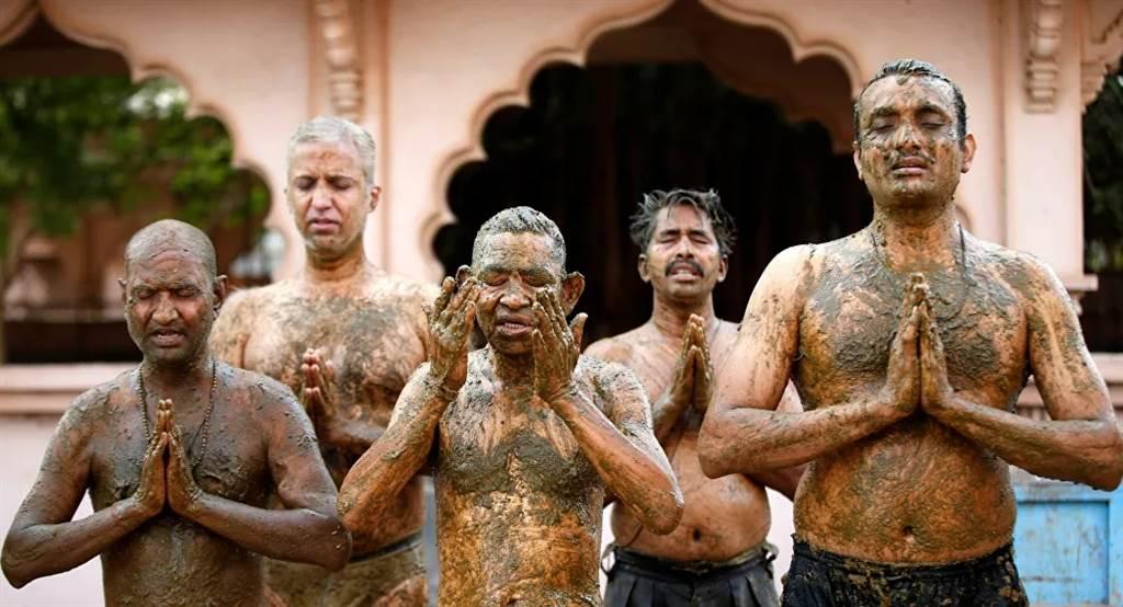 印度人迷信牛糞尿可治新冠,塗滿全身,再虔誠祈禱。(圖/路透)