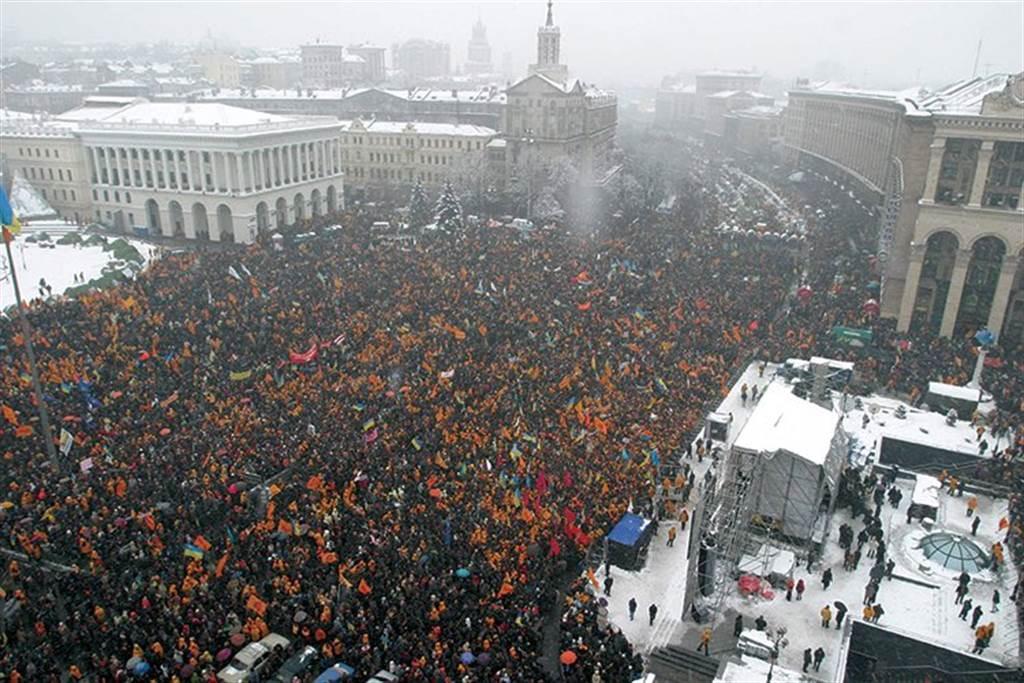 一般政治評論認為,2004年起由西方國家策動的「橙色革命」,在2014年時趕走了親俄的烏克蘭總統,是改變烏克蘭政局的關鍵事件。自此烏克蘭政治失序,族群與黨派惡鬥中逐漸沉淪。圖為2004年在基輔的橙色革命。(圖/推特@KatyaYushchenko)