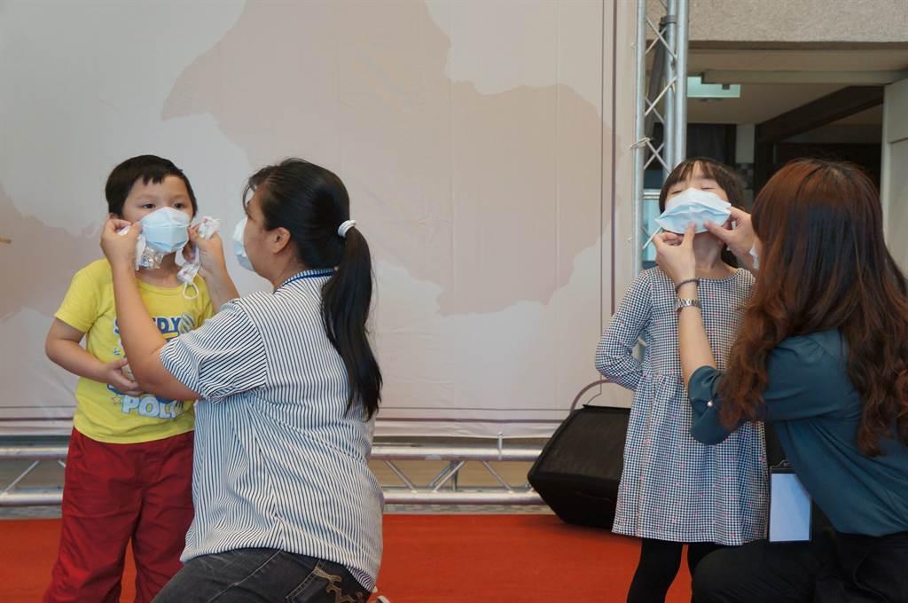 學童示範戴上無耳掛黏貼式口罩。(王文吉攝)