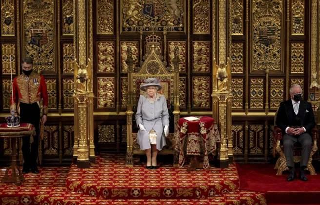 英國女王伊麗莎白2世主持英國議會開議,在右邊的是查爾斯王子,她的王冠在左邊枕頭上,由皇家衛兵把守著。(圖/美聯社)