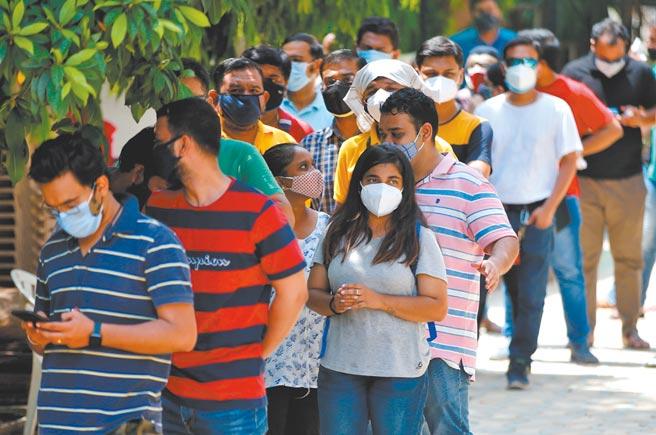 印度疫情失控,恐使该国的经济復甦停滞不前,全球也笼罩物资短缺危机。图为排队接种疫苗的印度民眾。图/路透