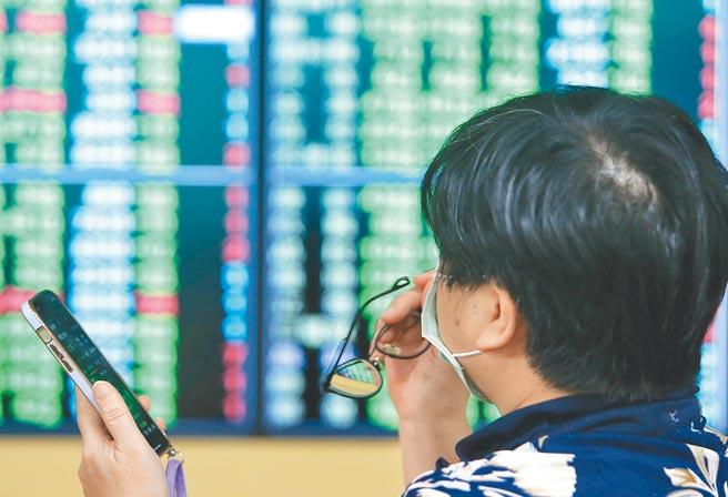 台北股市11日開低走低,最高下跌超過700點,午盤過後逢低買盤進場承接帶動跌幅收斂,終場下跌652點,收在16,583點,號子裡面投資人拿著手機同時關注兩邊盤面上的走勢。(季志翔攝)