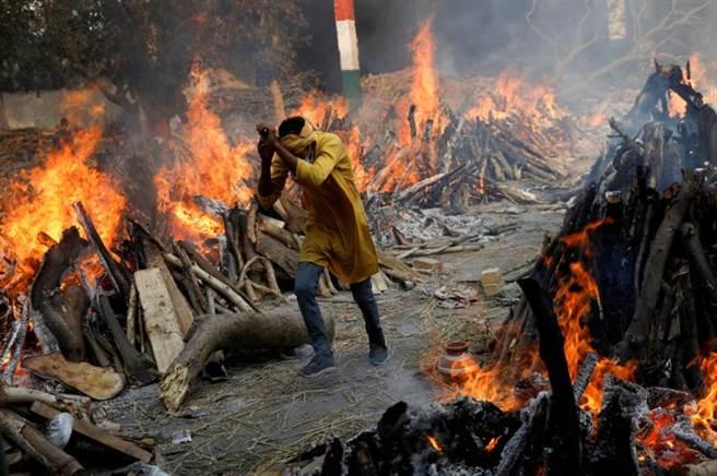 在印度出現的雙變異B.1.617病毒株不只沒有受到炎熱天氣壓抑,反而快速傳播,印度醫療體系面臨崩潰,北印度大量病患與病死者問題,在國際媒體報導下猶如人間煉獄。圖為新德里的火葬場上一名工作人員躲避焚燒屍體的熱氣。(圖/路透)