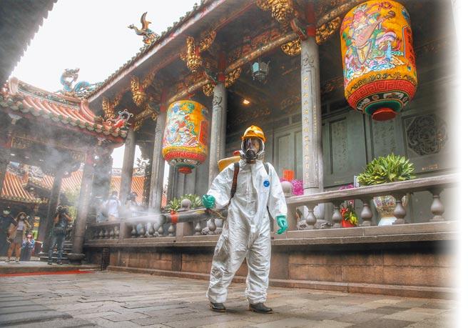 新冠肺炎疫情進入社區感染,台北市萬華區也出現2名茶藝館工作人員確診,12日環保局人員進入萬華龍山寺及周邊緊急進行防疫消毒。(王英豪攝)