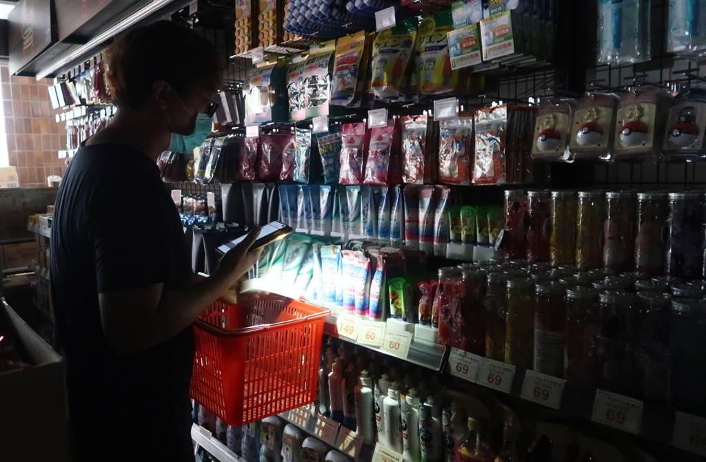 興達電廠13日因事故全廠停機,台北市有許多商家亦停電,民眾摸黑以手機照明選購商品。(資料照/王英豪攝)
