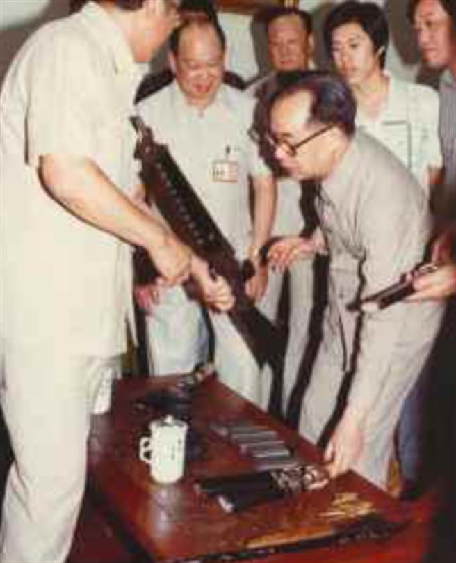 1981年時任法務部長李元簇(右),退休後於1996年檢視蘇俊模搶運鈔車的槍枝。(中時資料照)