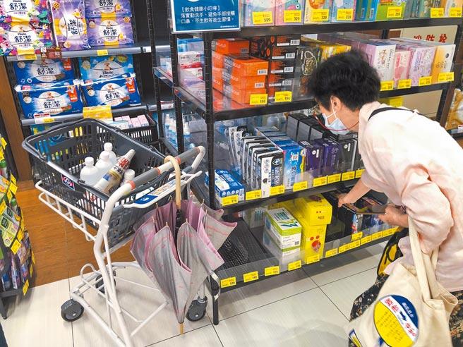 疫情升溫,不少民眾搶購民生和防疫物資,業者也積極備貨,圖為全聯中正延平店民眾選購口罩。(吳松翰攝)
