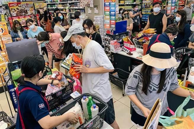 疫情再度升溫,雙北升為三級防疫警戒,15日中央開記者會後,賣場立刻湧入大批民眾搶購物資,排隊隊伍包圍整個賣場,每位消費者至少等一小時才能結帳。(鄧博仁攝)
