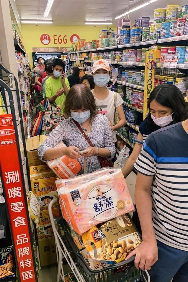 疫情再度升溫,雙北升為三級防疫警戒,15日中央開記者會後,賣場立刻湧入大批民眾搶購物資,從排隊到結帳,至少等候一小時。(鄧博仁攝)