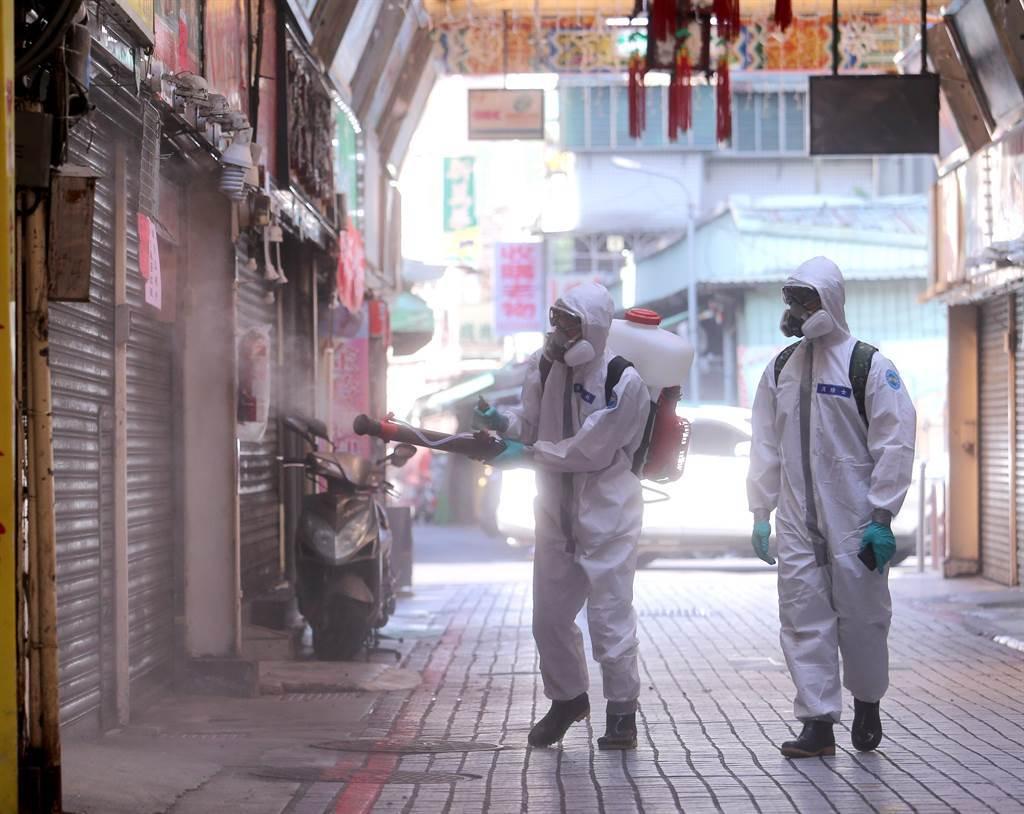 以往熱鬧的華西街商圈,多數商家都已拉下鐵門暫停營業,兩人一組的化學兵仔細清消。(黃世麒攝)