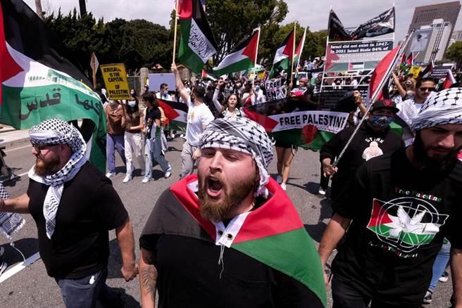 在洛杉磯的威斯伍德(Westwood)地區,示威者手持標誌向以色列領事館行進,以支持巴勒斯坦。(圖/美聯社)