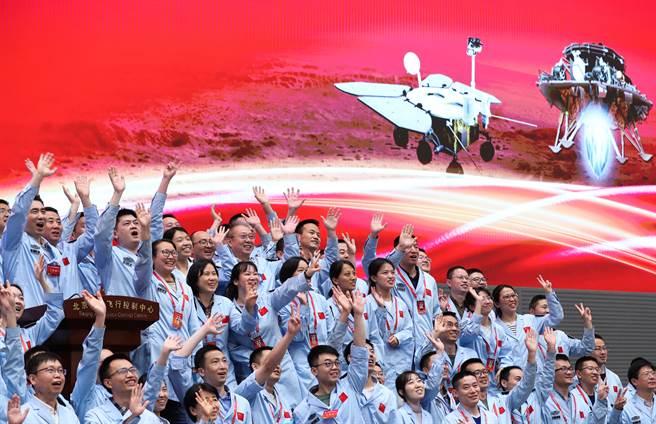 中國大陸航天科研人員在北京航天飛行控制中心指揮大廳,慶祝首次火星探測任務著陸火星成功。(圖/新華社)