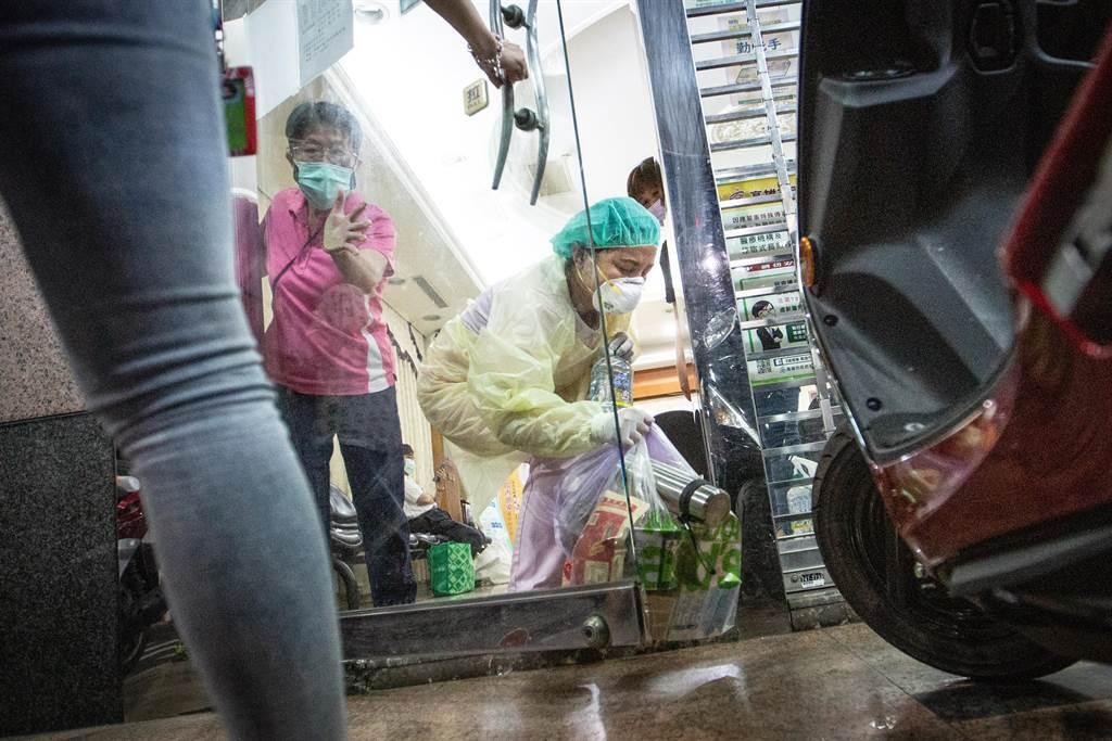 家屬替即將前往檢疫、隔離的員工送來隔離物資,交付過程均仔細消毒。(袁庭堯社)