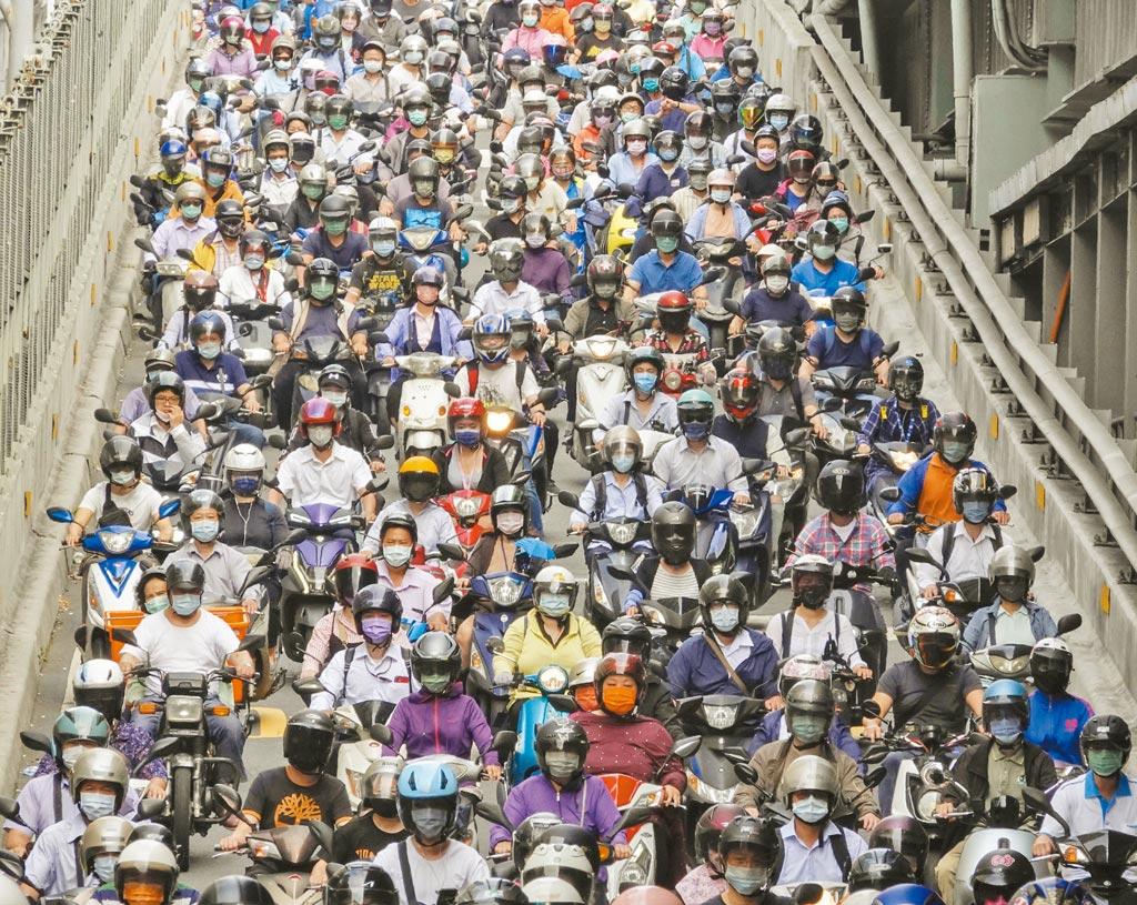 台灣本土疫情持續爆發,短短8天確診就累計達1024例,最多確診數仍落在雙北,許多民眾都提高警覺加強防疫,連通新北三重與台北大同兩區的台北大橋,陣容龐大的通勤機車族幾乎人人戴著口罩,但流量驚人的車陣讓維持社交距離成為不可能的任務。(黃子明攝)