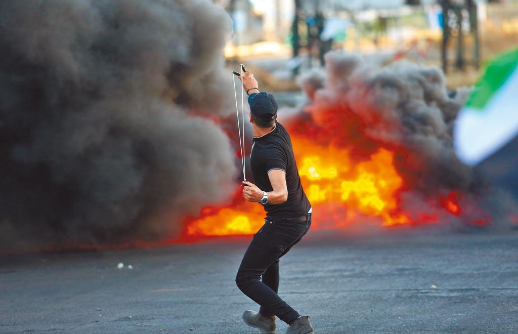 以巴衝突進入第2周,並無緩和跡象,且從加薩蔓延至約旦河西岸。圖為17日在約旦河西岸城市納布盧斯,一名巴勒斯坦抗議者以彈弓朝以色列部隊發射石頭。(新華社)