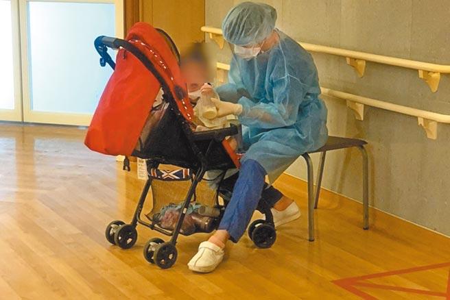 台北慈濟醫院護理師許斐粧在護理站照顧確診後、剛解除隔離的1歲女嬰,畫面動人,大批網友替醫護加油打氣。(台北慈濟醫院提供/葉書宏新北傳真)