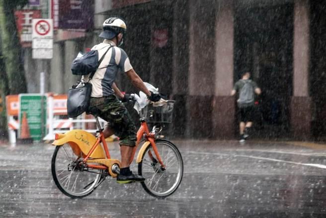 今天(31日)受到滯留鋒面影響,午後嘉義以北及宜花地區雨勢增強,15縣市出現局部大雨或豪雨。圖為未帶雨具出門的路人,只好往前衝。(鄧博仁攝)