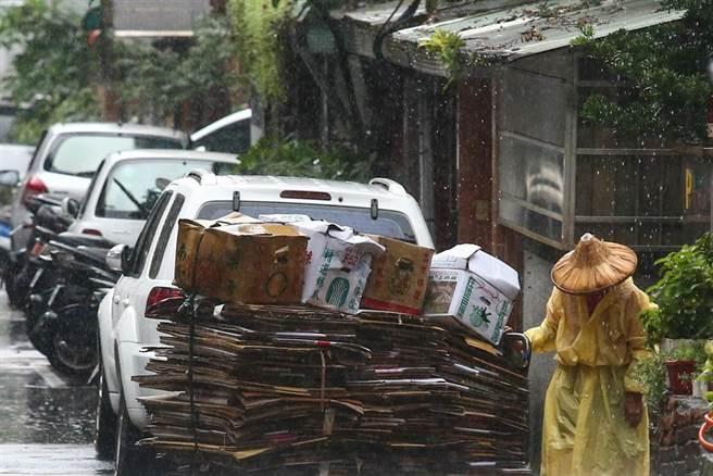 滯留鋒面帶來雨量驚人,氣象局今(31)一度針對15縣市發布豪大雨特報。圖為一位婦人在大雨中,整理著被雨打溼的資源回收車。(鄧博仁攝)