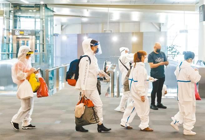 松山機場旅客全身穿著防護衣準備登機。(圖非當事人,郭吉銓攝)