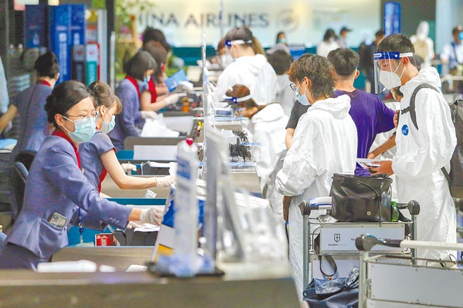 國內疫情嚴峻,除返美潮外,也有許多境外生離台,使得桃園機場出現難得人潮。圖為3日旅客身穿防護裝備辦理出境登機手續。(陳麒全攝)
