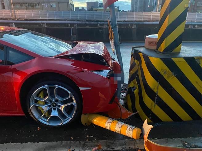 新北市板橋警分局今(7日)凌晨4時許獲報,紅色藍寶堅尼超跑行經板橋區台64線快速道路下板橋出口處自撞分隔道車頭全毀。(葉書宏翻攝)