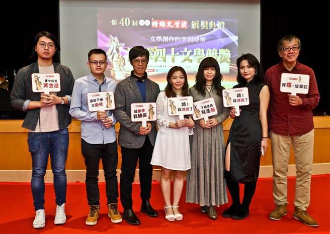 由旺旺中時媒體集團所主辦的第40屆「旺旺・時報文學獎」頒獎,參賽者們拿著舉牌開心合影。(資料照片)