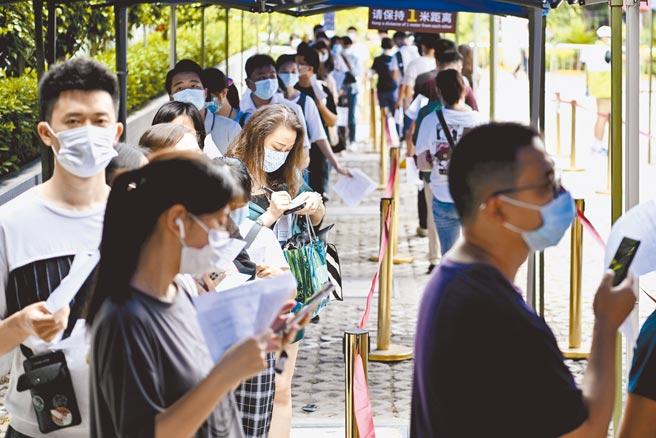 市民排隊進入新冠疫苗接種點 。(中新社)