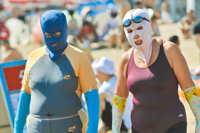 臉基尼為尼龍頭套,原本是大陸大媽防曬所發明,後來風靡全球。圖為山東省青島市,戴著臉基尼頭罩的大媽在第一海水浴場下海游泳。(中新社)