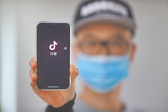 大陸十三屆全國人大常委會10日表決通過《反外國制裁法》,賦予中國政府、企業、個人以及法庭主動反擊權。圖為1位北京市民展示手機上的抖音app。(中新社)
