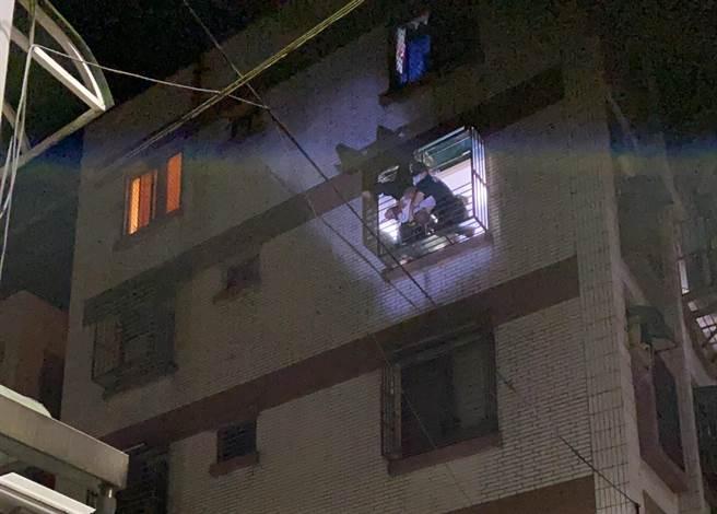 王男因未帶鑰匙,欲從自家頂樓爬窗返家,不慎失足,右腳卡進4樓住家遮雨棚,倒掛在防盜窗框外圍。(基隆市消防局提供/陳彩玲基隆傳真)