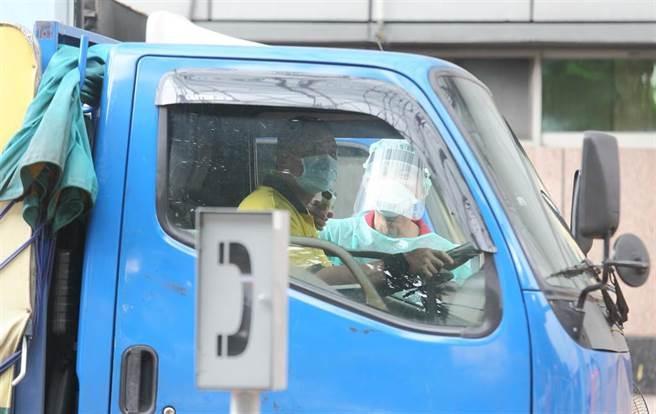 台北農產運銷公司群聚擴大,第二果菜批發市場車輛入口都有工作人員進行實聯制管制與量測體溫。(資料照/張鎧乙攝)