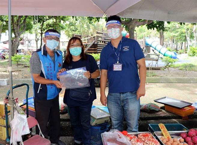 嘉義市政府建設處長田長沛(左)代表轉贈防護面罩給共和市場的攤商。(廖素慧攝)