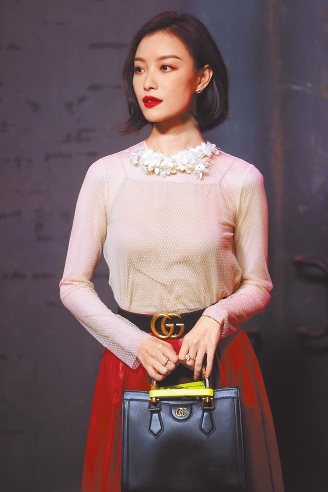 倪妮以裸色鏤空衫搭配大紅裙出席時尚秀。(CFP)