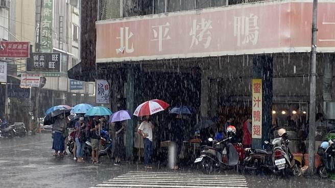 台中市向上市場的知名土窯雞烤鴨店,雖下雨還是見撐傘排隊人潮。(陳淑芬攝)
