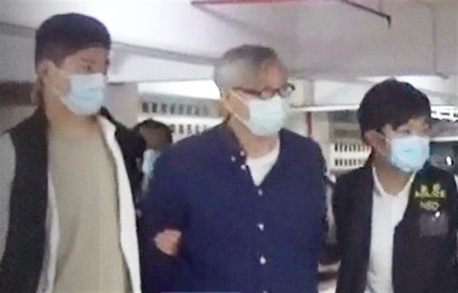 香港《蘋果日報》前主筆、英文版執行總編輯馮偉光(中)昨晚準備搭機離港時,被香港警方國安處人員以涉嫌勾結外國勢力拘捕,至今日凌晨仍被扣押在機場警署。(東網)