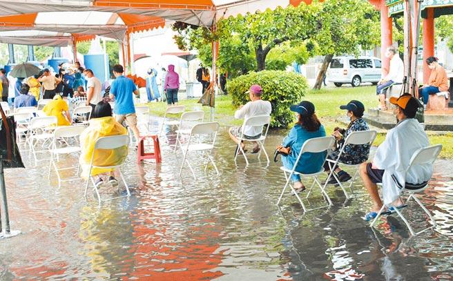 屏東枋寮國小篩檢站啟動首日因下起大雨,不少民眾泡在水裡,排隊等待篩檢。(林和生攝)
