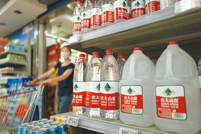 農夫山泉創辦人鍾睒睒因旗下產品「拂曉白桃味蘇打氣泡水」捲入日本福島風波,身價暴跌不再是亞洲首富。圖為北京市一家超市貨架上擺放的農夫山泉飲用水。(中新社)